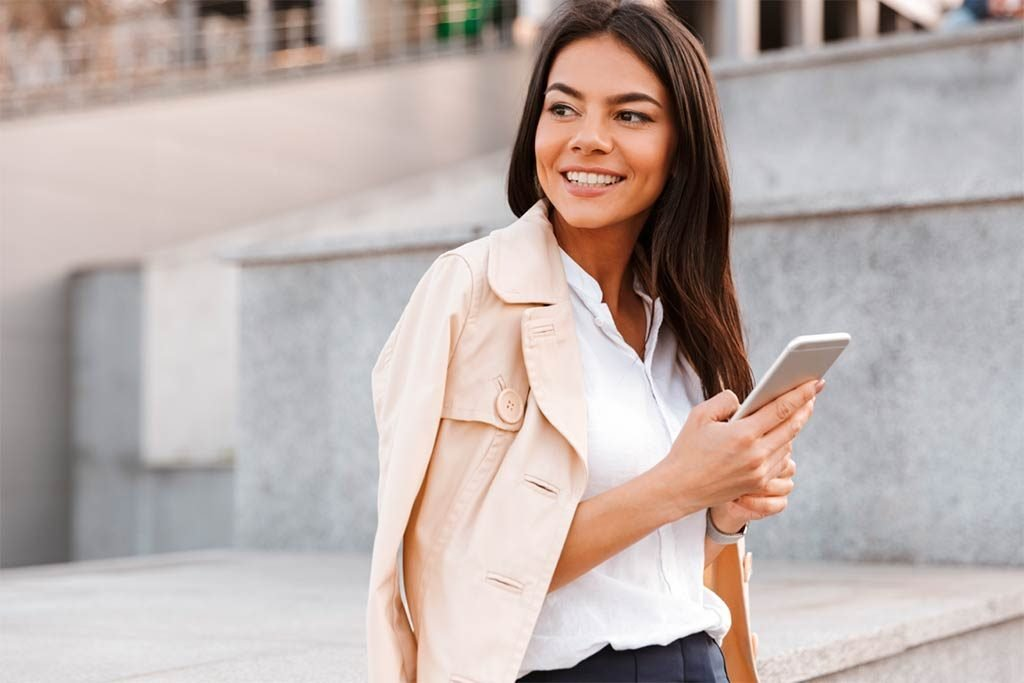 Young executive woman on the street using the cell phone to book a hotel in the takeabed application. Then he will share the link with his friends to earn money.