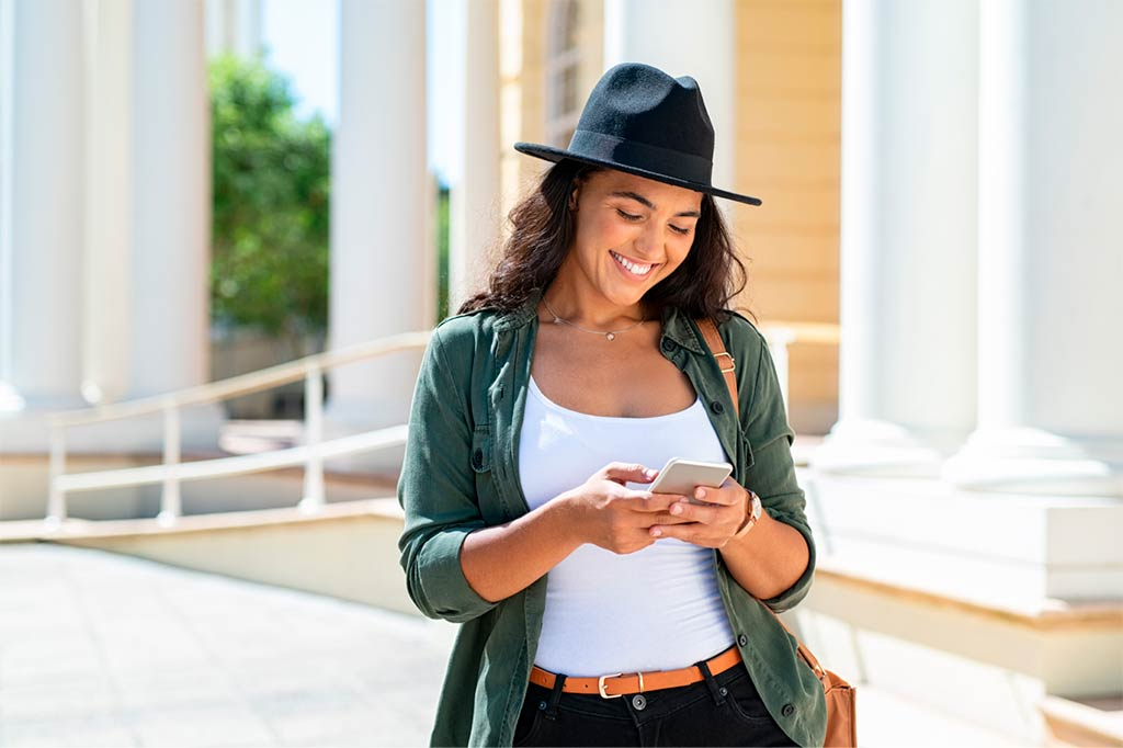 Funny young woman wearing hat and walking in the sun. He is using the takeabed application on his cell phone, looking for cheap hotels to travel.