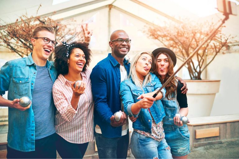 Group of friends, women and men taking a selfie smiling happy. Everyone goes on a trip together with a cheaper hotel reservation that they took out with takeabed.