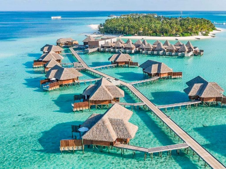 Hotel in Maldives. Cabins on the crystalline ocean. A paradise on earth. The water is transparent, the fish can be seen swimming. There are no people in the photo, only the hotel, the ocean, the sun and nature.