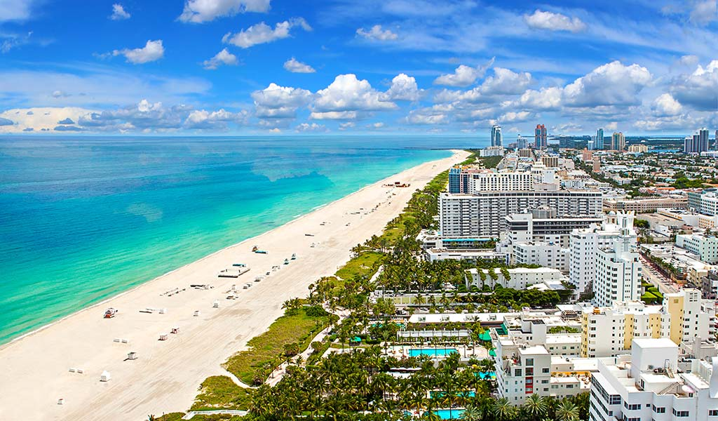 Aerial view of the Miami Beach beach. You can see the hotels, their pools, the white sand and the blue sea.