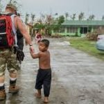 Marine holding the hand of a little boy